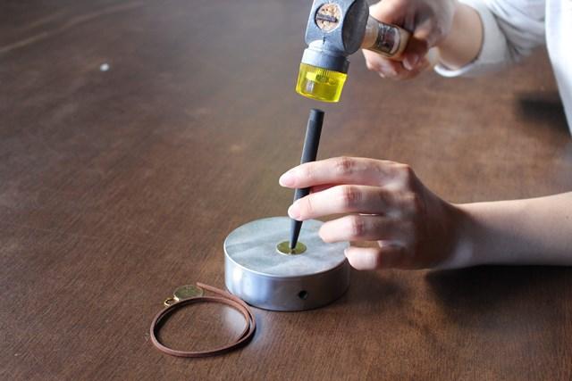 利用金工基礎技法,在薄金屬片上進行敲鎚,呈現出點字、英文字或其他花樣效果,打造專屬的小墜子(黃金博物館提供)